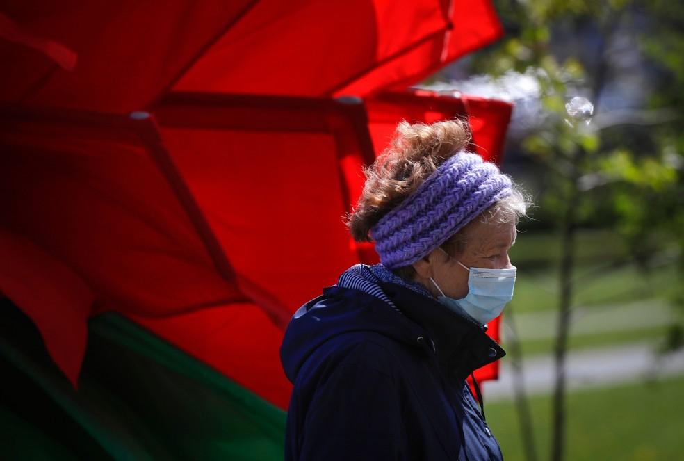 Uma mulher com máscara passa por bandeiras nas cores vermelho e verde enquanto a cidade de Minsk, em Belarus, se prepara para o desfile militar do Dia da Vitória que ocorrerá no sábado (9)  — Foto: Sergei Grits/AP