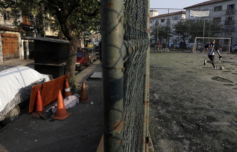 O corpo de Valnir Mendes da Silva, de 62 anos, é visto em uma calçada da comunidade de Arara, no Rio de Janeiro, em 17 de maio, onde morreu após moradores solicitarem ajuda dos serviços de emergência enquanto ele apresentava problemas respiratórios  — Foto: Ricardo Moraes/Reuters
