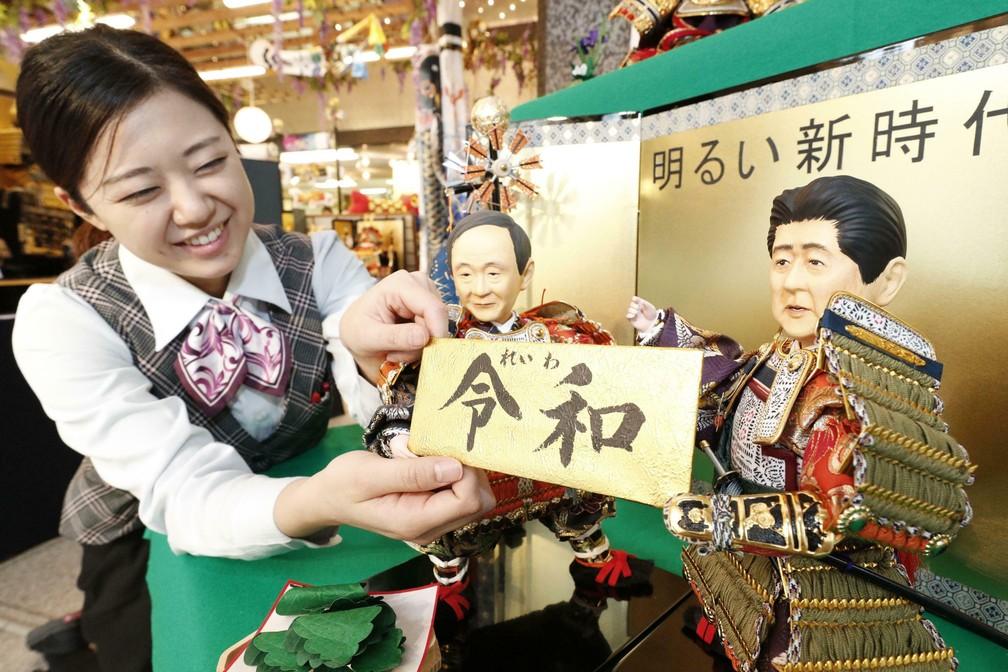 Vendedora segura placa com o nome da nova era imperial japonesa, Reiwa, em uma empresa de bonecas japonesa em Tóquio, no dia do anúncio, em 1º de abril. — Foto: Satoru Yonemaru/Kyodo News via AP