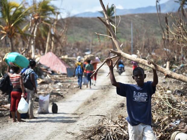Pessoas caminham por rua de Les Cayes, no Haiti, na segunda-feira (10). Cidade ficou devastada após a passagem do furacão Matthew (Foto: Hector Retamal / AFP)