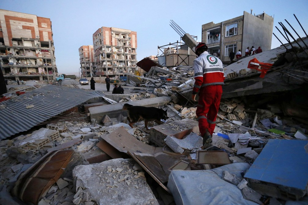 Funcionário do Crescente Vermelho realiza trabalho de busca para encontrar sobreviventes em destroços de prédio destruído na cidade de Sarpol-e-Zahab, após terremoto (Foto: Pouria Pakizeh/ISNA/AP)