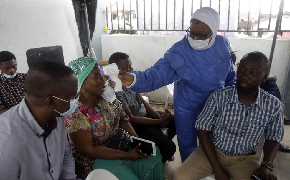 Enfermeira mede a temperatura de pessoas que se preparam para receber a vacina contra a Covid-19 da Moderna em Lagos, na Nigéria, em 25 de agosto de 2021 — Foto: Sunday Alamba/AP