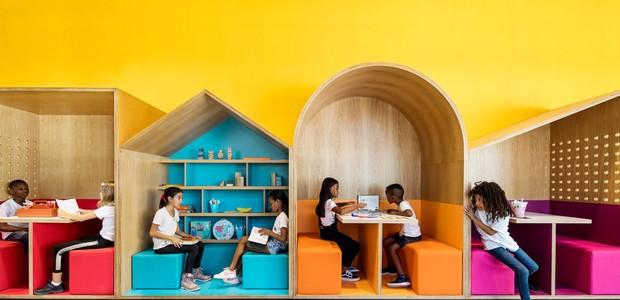 Cores vivas criam uma atmosfera lúdica nas áreas comuns da escola. Dentro de casinhas de madeira, os pequenos tem um espaço próprio para interagir e soltar a imaginação, com muito aprendizado. Além disso, a temática oferece experiências diferentes fora da (Foto:  Itay Benit/ Dezeen/ Reprodução)