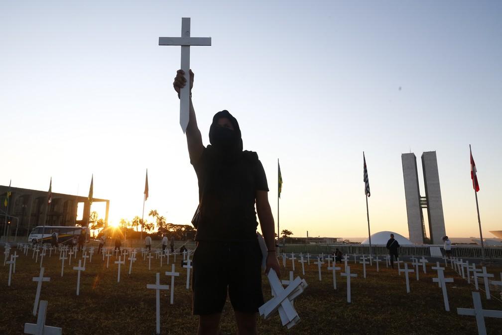 28 de junho: manifestante segura cruz simbolizando vítimas de Covid-19 em protesto contra o presidente Jair Bolsonaro em frente ao Congresso, em Brasília. — Foto: Sergio Lima/AFP