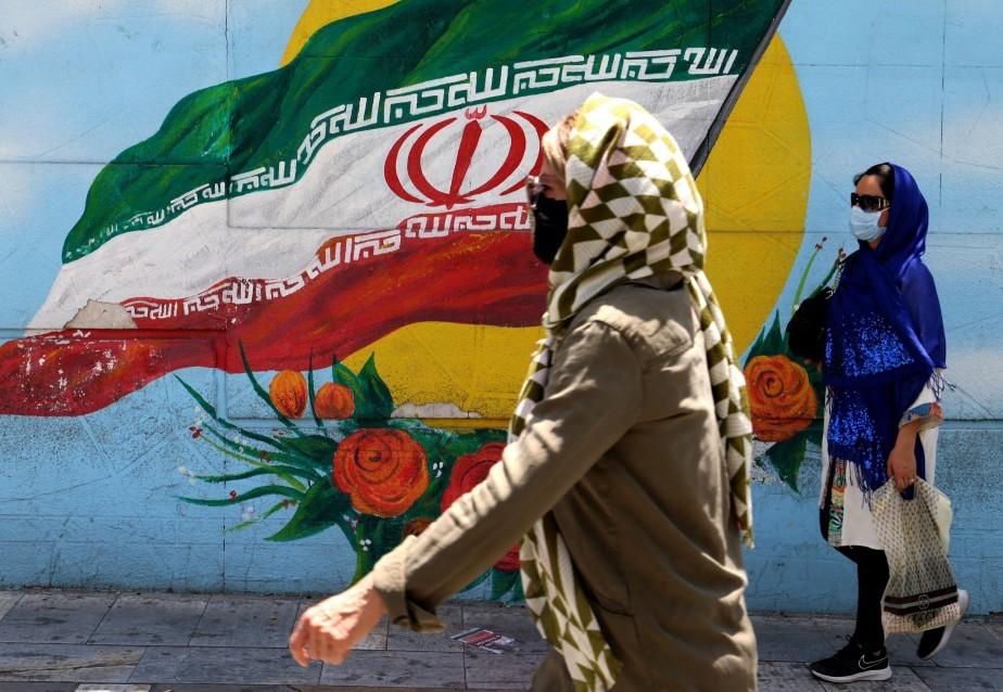 De máscara, mulheres caminham em frente à mural com a bandeira iraniana, em Teerã