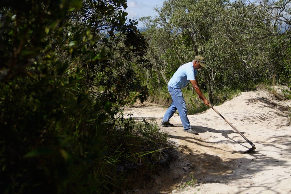 Parque Estadual do Ibitipoca - trabalhador puxa areia que se acumula nas trilhas pelo pisoteio — Foto: Dimas Stephan/G1