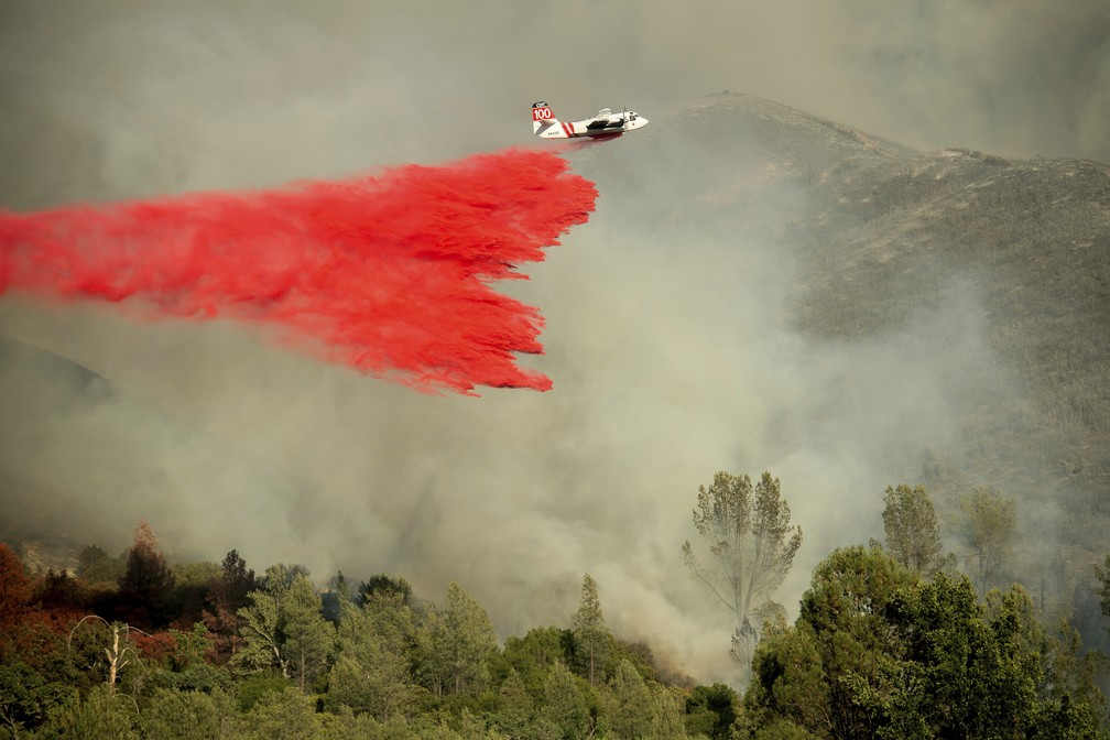 Avião joga produto especial para tentar apagar chamas de incêndio florestal na Califórnia (Foto: Noah Berger/AP)