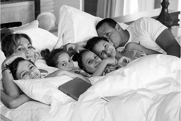 Jennifer Lopez e Alex Rodriguez em uma cama na companhia de seus filhos de relacionamentos prévios (Foto: Instagram)