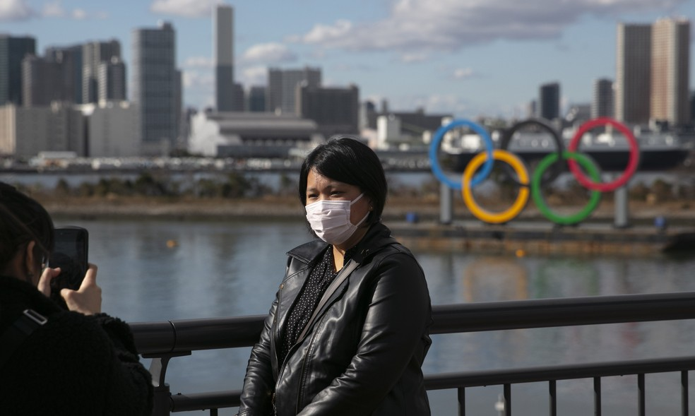 Turista com máscara posa para foto em frente aos anéis olímpicos na Baía de Tóquio, no Japão — Foto: Jae C. Hong, File / AP Photo