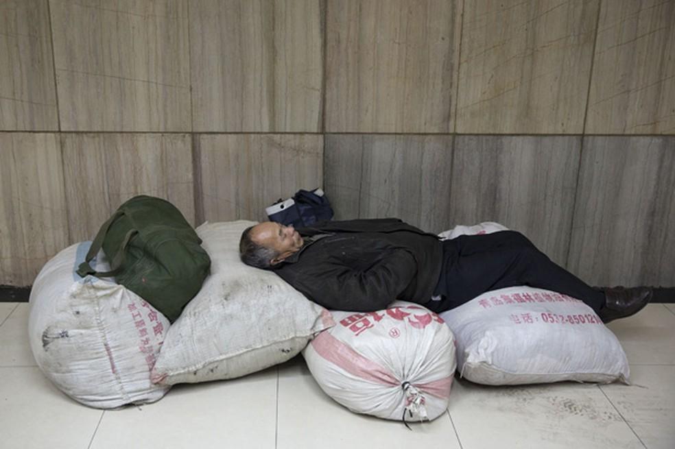 Passageiro usou bagagem para montar 'cama king size' em estação de trem em Pequim, na China — Foto: Alexander F. Yuan/AP/Arquivo