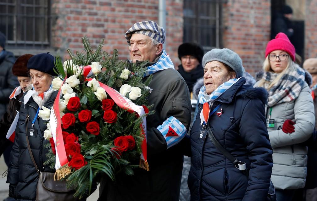 Sobreviventes carregam uma coroa de flores em Auschwitz, na Polônia, nesta segunda-feira (27)  — Foto: Aleksandra Szmigiel/ Reuters