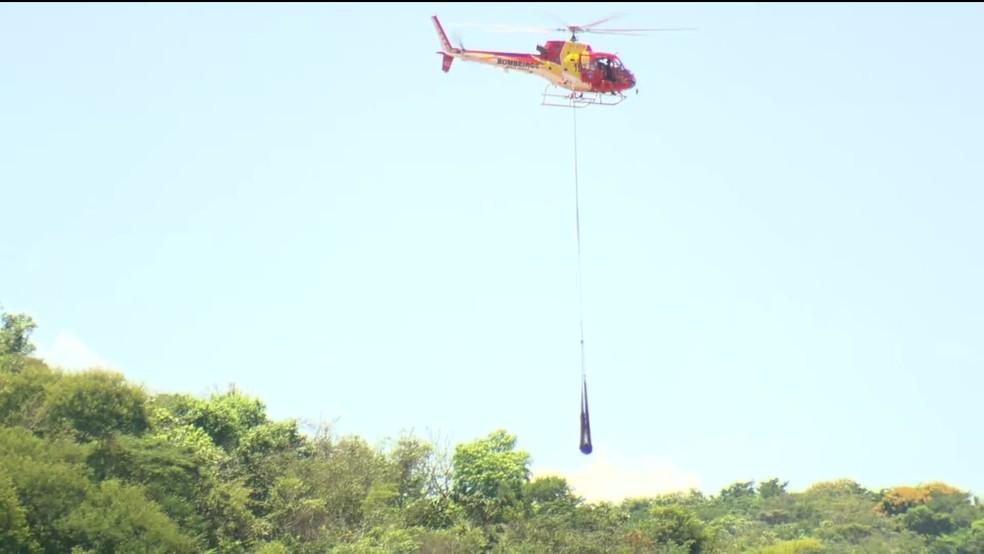 Helicóptero faz o transporte de corpo retirado da lama em Brumadinho — Foto: Reprodução/GloboNews