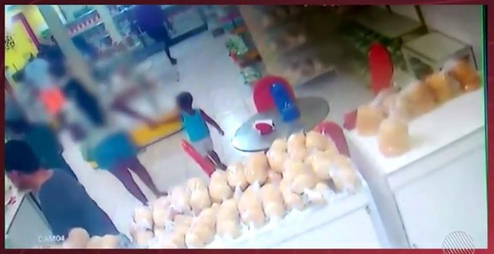 Uma das crianças circula pela padaria de mãos dadas com uma mulher durante o assalto (Foto: Reprodução/TV Subaé)