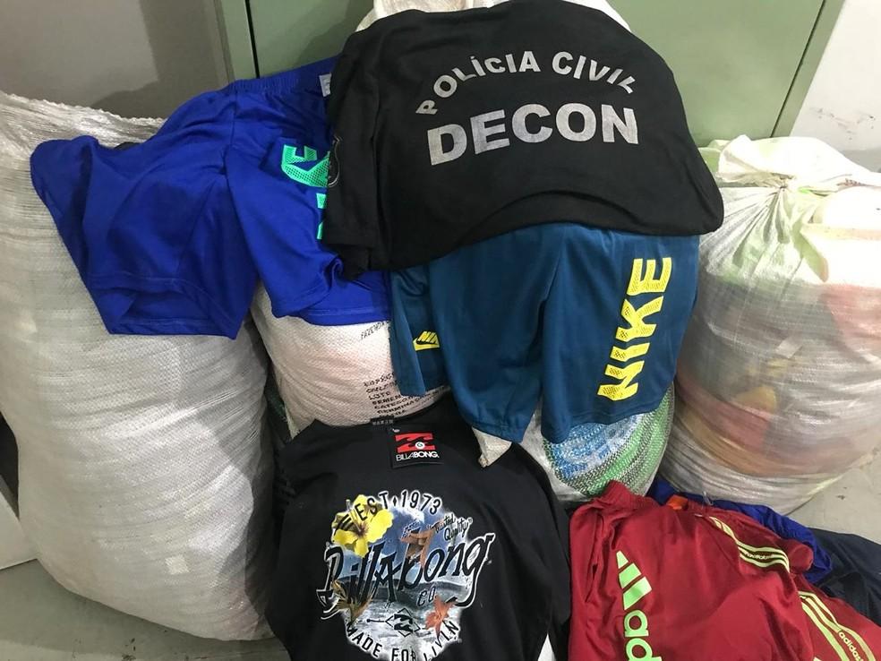 No local, os policiais encontraram peças réplicas de bermudas, camisetas e calças das marcas — Foto: Polícia Civil de Mato Grosso/Assessoria