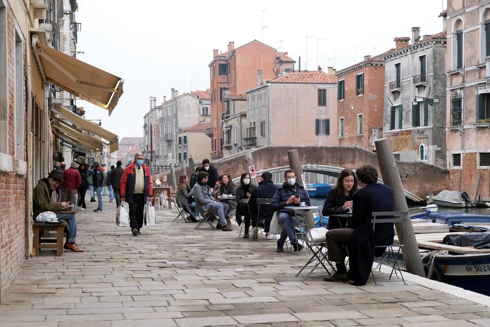 Pessoas sentadas em restaurantes em Veneza às margens de canal nesta sábado (14) — Foto: Manuel Silvestri/Reuters