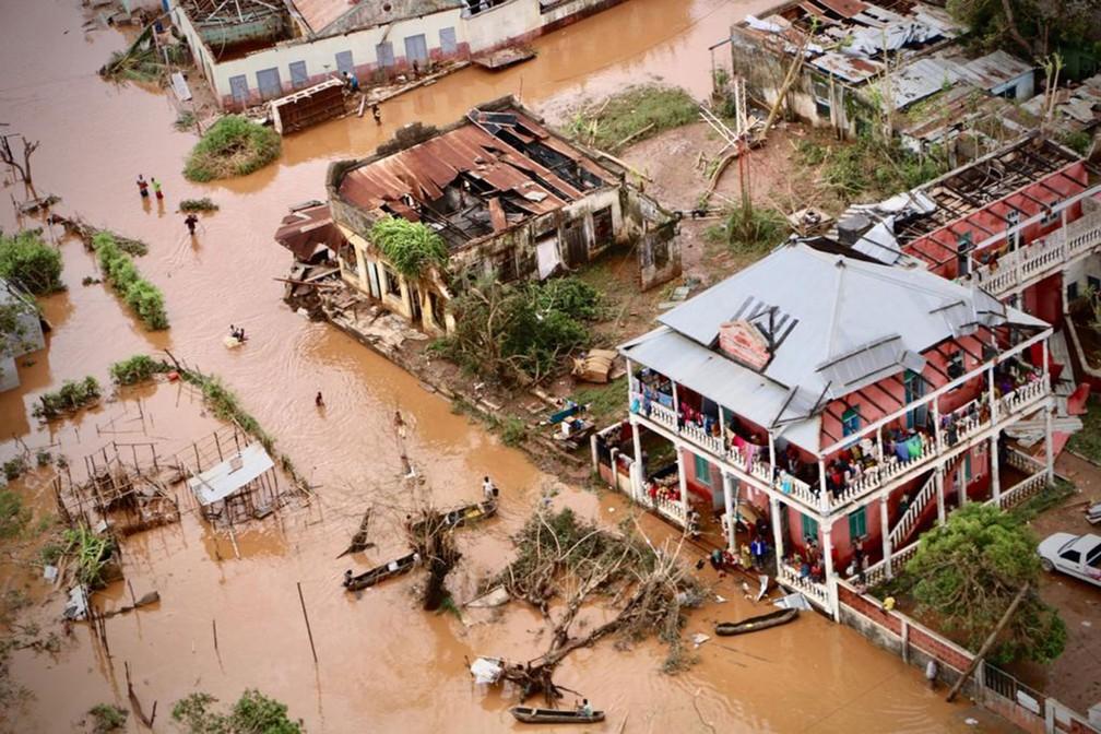 Pessoas caminham em rua inundada da cidade de Buzi, na quarta-feira (20)  — Foto: Adrien Barbier / AFP