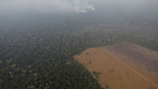 Em foto do último dia 21, fumaça se espalha em área de floresta parcialmente desmatada perto de Porto Velho (RO), um dos dez municípios citados no estudo (Foto: REUTERS/UESLEI MARCELINO/BBC)