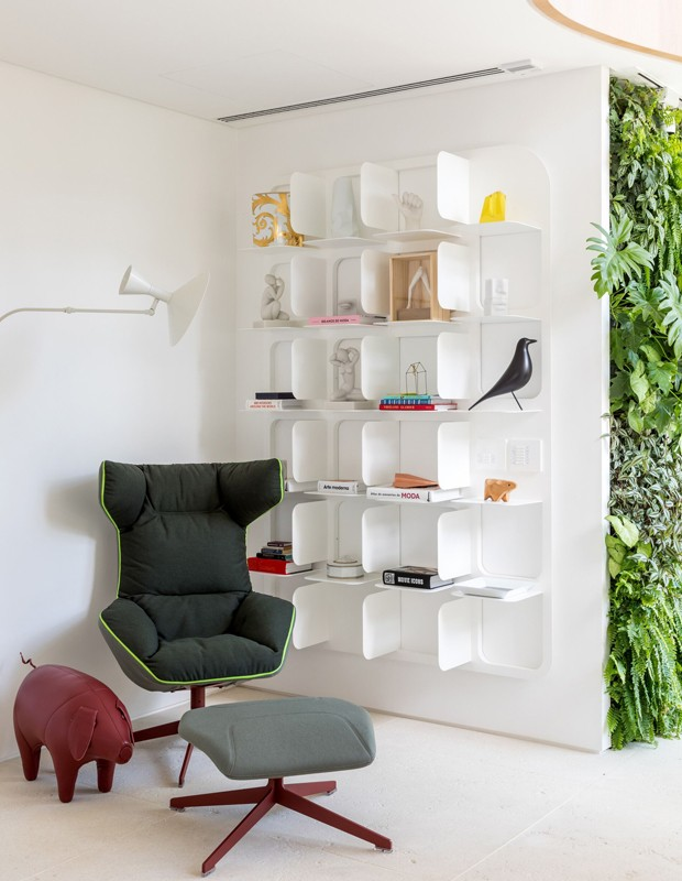 No hall, um cantinho para relaxar e apreciar um bom livro. Estante com nichos e jardim vertical compõe o ambiente (Foto: Fran Parente/Divulgação)