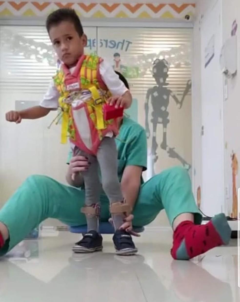 Dudu andando com a ajuda da fisioterapeuta — Foto: Arquivo Pessoal/Caroline Araujo