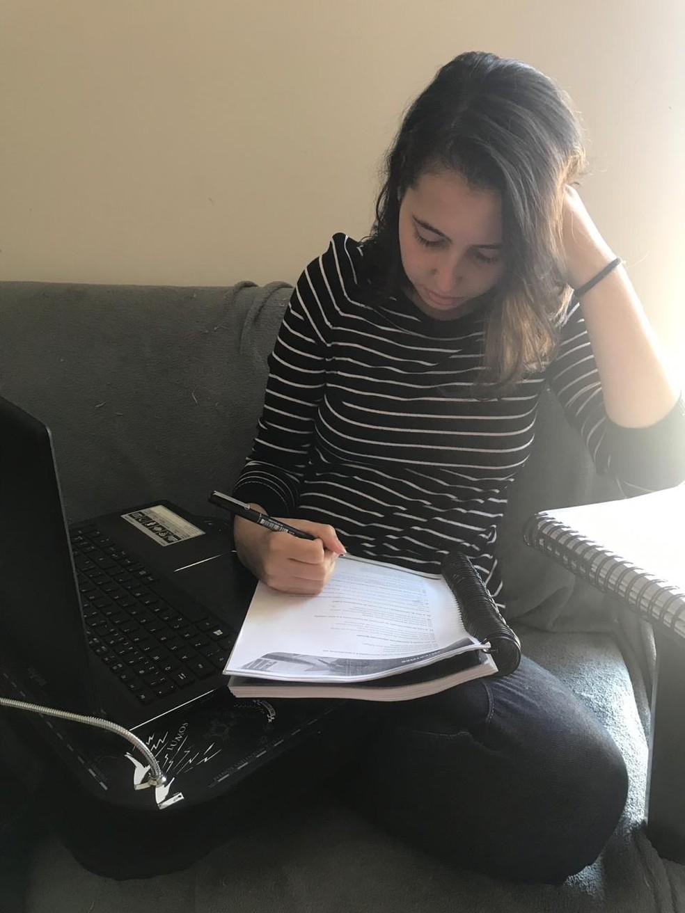 Nathalia estuda no sofá de casa para a prova que se prepara — Foto: Victor Regis