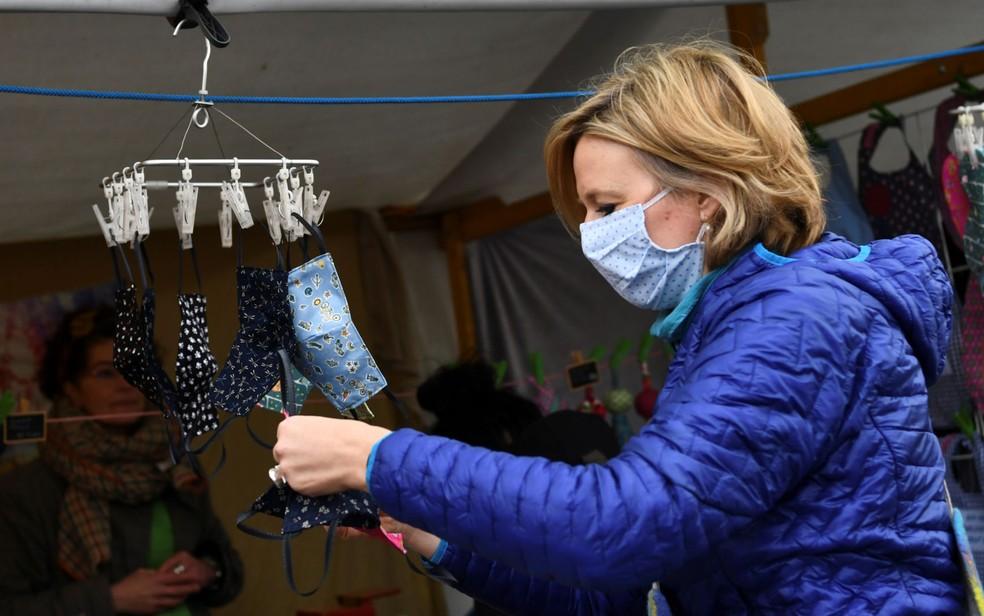 Mulher observa máscaras à venda em mercado de rua em Berlim, na Alemanha, no sábado (25) — Foto: Annegret Hilse / Reuters