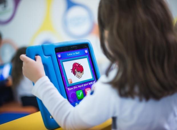 criança segurando tablet (Foto: Agência Ophelia)