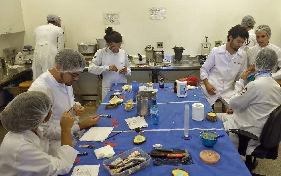 Professora Aline Úrsula (à direita) auxilia estudantes na confecção das próteses faciais (Foto: Marília Marques/G1)