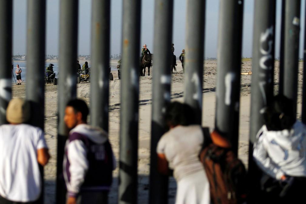 Migrantes que chegaram à cidade de Tijuana (México) na terça-feira (13) observam patrulha na fronteira americana. Eles fazem parte de uma caravana com milhares de pessoas que tentam entrar nos EUA — Foto: Jorge Duenes/ Reuters