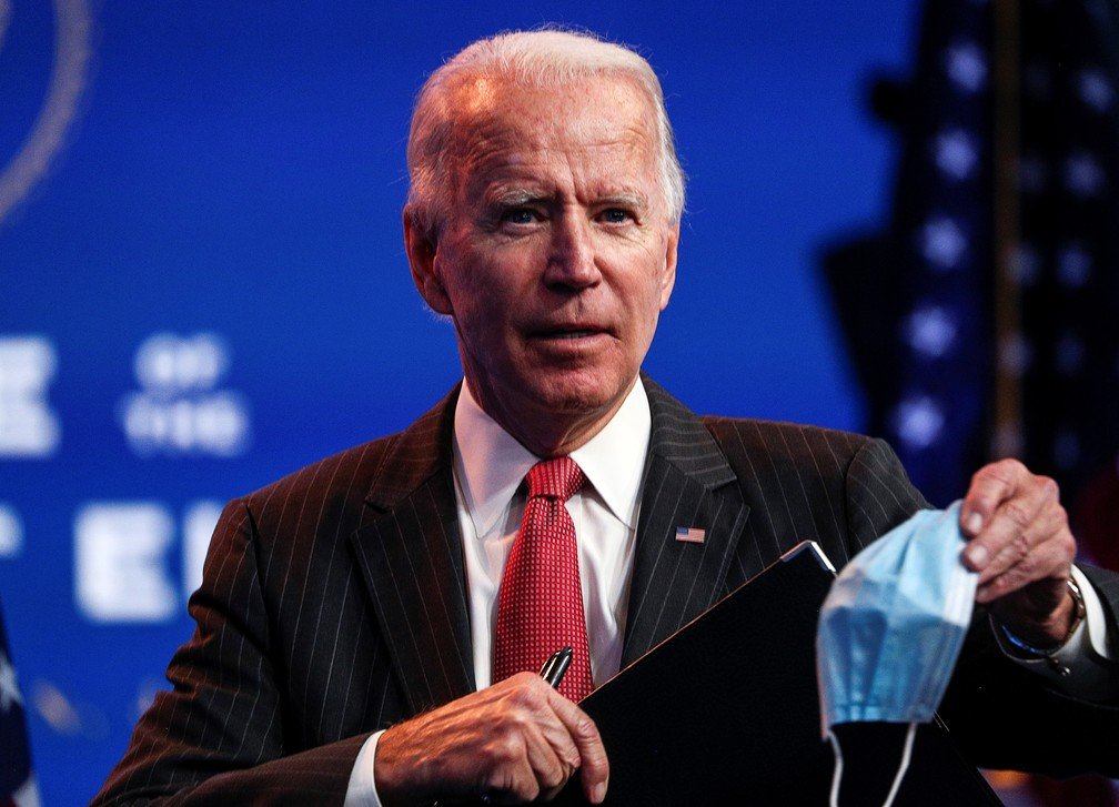 Presidente eleito dos EUA, Joe Biden, tira a máscara para falar a jornalistas durante entrevista coletiva em Wilmington nesta quinta-feira (19) — Foto: Tom Brenner/Reuters