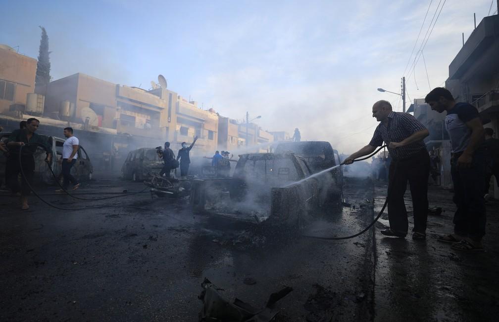 Homem joga água após explosão de carro bomba em Qamishli, na Síria, nesta sexta-feira (11) — Foto: Rodi Said/Reuters
