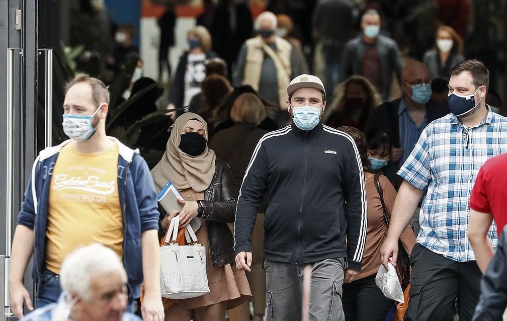 Pessoas usam a máscara facial obrigatória devido à pandemia de coronavírus em um shopping center em Essen, na Alemanha, na terça-feira (1º)  — Foto: Martin Meissner/AP
