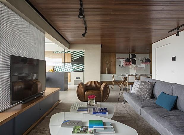 A área social - varanda, sala de estar e sala de jantar - foi toda integrada, enquanto a cozinha segue fechada. Iluminação da Reka (Foto: Gui Morelli/Divulgação Produção: Núria Uliana)