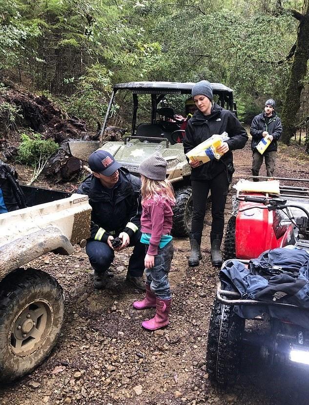 Policial conversa com a pequena Carolina, de 5 anos, pouco depois de encontrá-la em bosque (Foto: Reprodução Facebook)