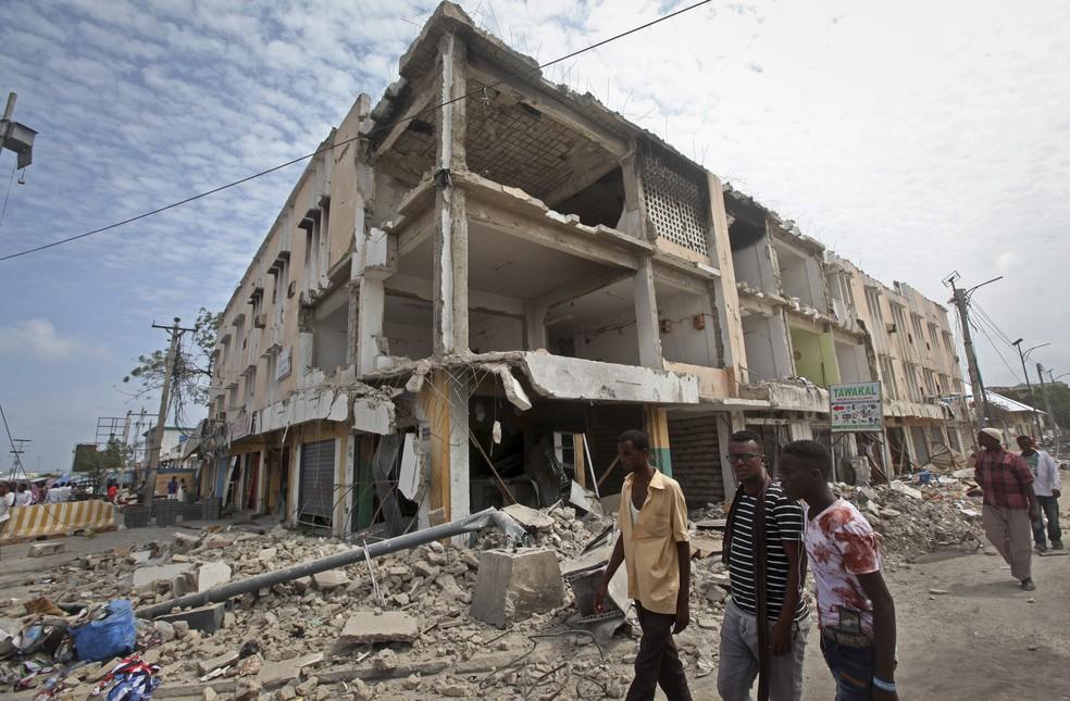 Homens caminham em frente a prédio destruído no local do ataque do último sábado em Mogadíscio (Foto: AP Photo/Farah Abdi Warsameh)