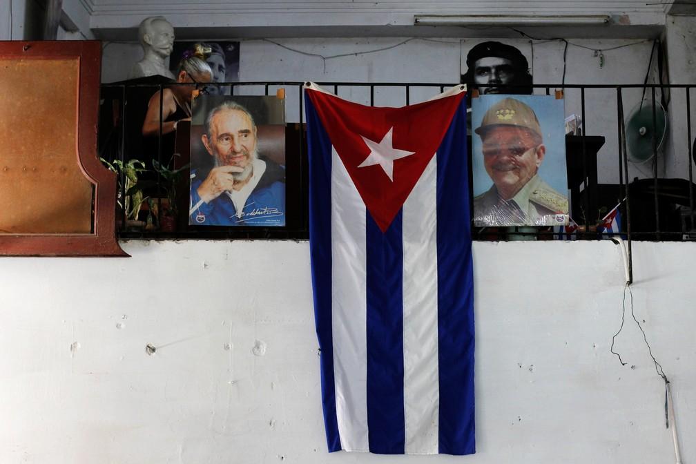 Bandeira de Cuba é clicada pendurada ao lado de fotografias de Raúl e Fidel Castro — Foto: Reuters/Stringer