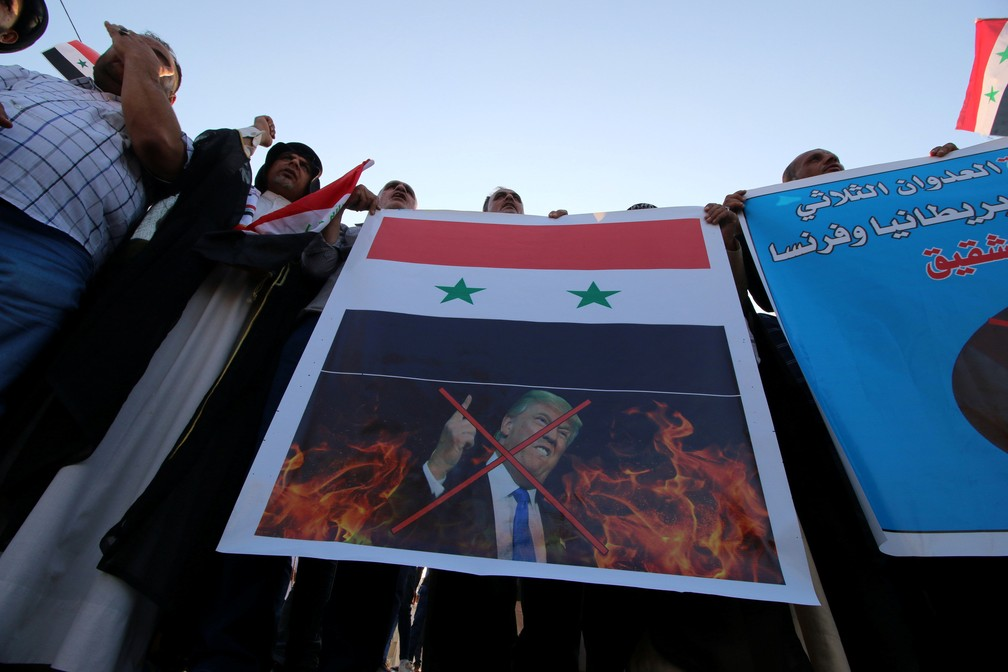 -  Manifestantes iraquianos carregam foto do presidente dos Estados Unidos Donald Trump em protesto contra ataque à Síria  Foto: Essam Al-Sudani/Reuters