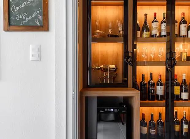 Uma pequena adega refrigerada ganha espaço na parte de baixo armário. A iluminação traseira valoriza os rótulos enfileirados (Foto: Airbnb/ Reprodução)