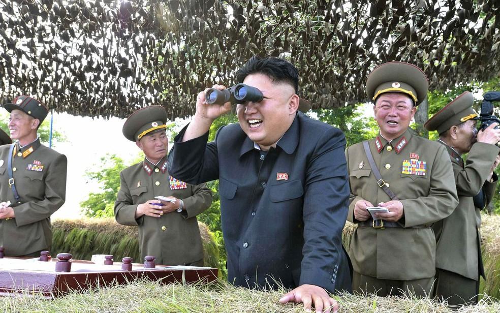 O ditador da Coreia do Norte, Kim Jong-un, sorri enquanto observa com binóculos um grupo militar norte-coreano mantendo guarda à frente de um posto na costa leste da península coreana (Foto: Reuters/KCNA)