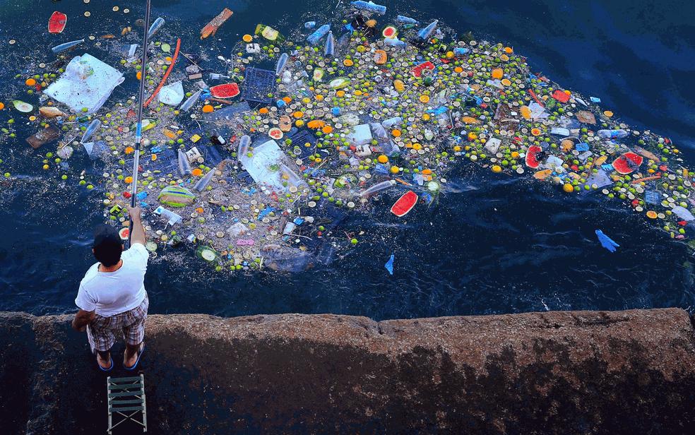 Homem pesca em meio ao lixo na costa do Mar Mediterrâneo em Beirute, no Líbano. (Foto: Hassan Ammar/AP/Arquivo)
