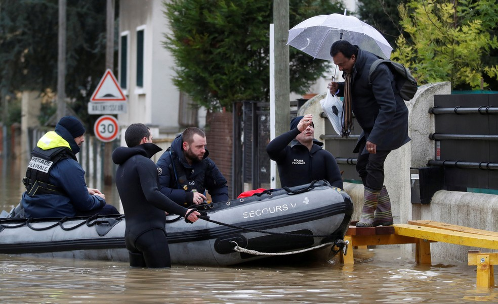Mergulhadores da polícia de Paris usam um pequeno barco para ajudar um morador a sair de casa enquanto patrulham uma rua inundada de uma área residencial em Villeneuve-Saint-Georges, perto de Paris, nesta quinta (25) (Foto: Christian Hartmann/Reuters)