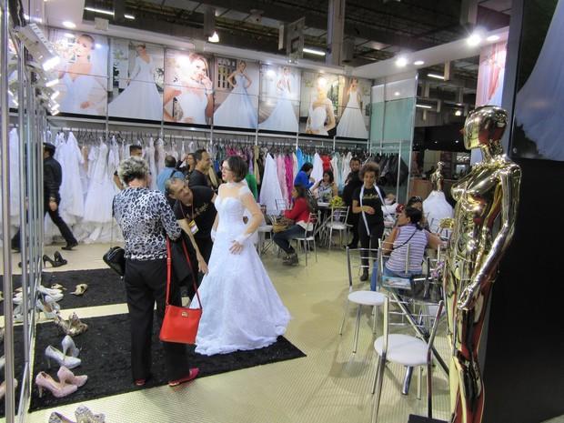 Noiva experimenta vestido em feira de São Paulo (Foto: Karina Trevizan/G1)