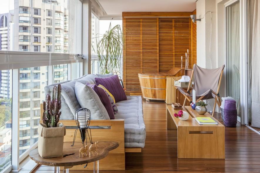 Sofá e mesa de centro de madeira, poltronas e futons da Futon Company, mesa lateral da Tora Brasil na varanda do apartamento dos arquitetos Rodrigo Costa e Alessandra Marques, do Studio Costa Marques