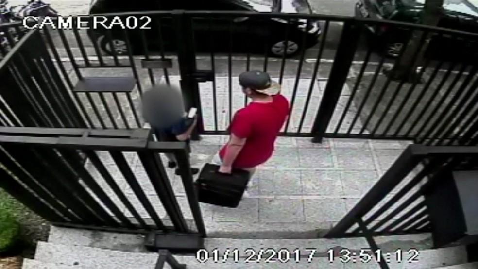 Após assalto, ladrões saem com uma mala com o cofre do apartamento (Foto: TV Globo/Reprodução)
