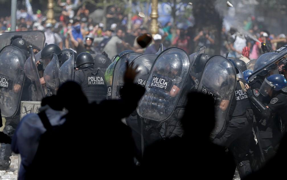 Policiais se protegem de pedras atiradas por manifestantes durante confrontos em frente ao Congresso Nacional em votação pela reforma da previdência, em Buenos Aires, na Argentina, na segunda-feira (18) (Foto: AP Photo/Natacha Pisarenko)