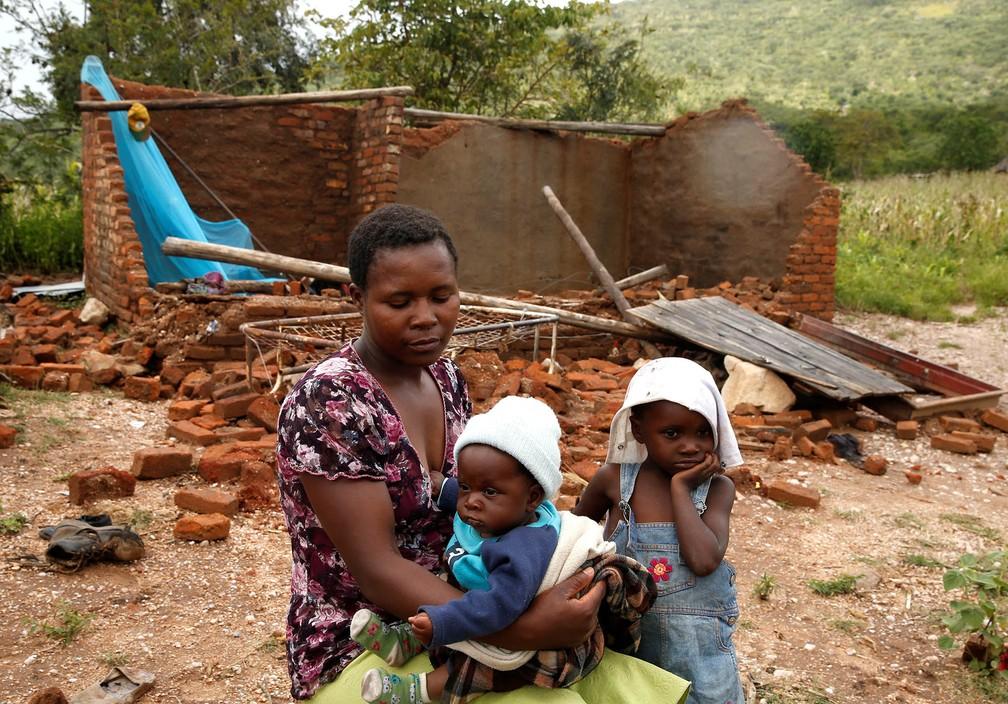 Nomatter Ncube senta-se com seus filhos diante de sua casa destruída pela passagem do ciclone Idai em Chimanimani, Zimbábue — Foto: Philimon Bulawayo/Reuters
