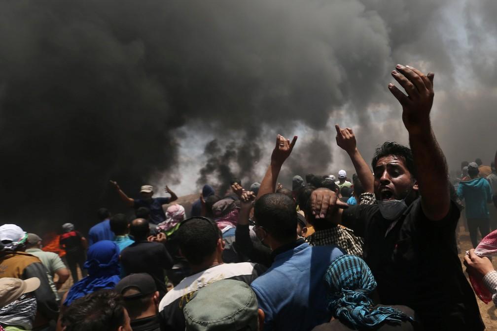 Manifestantes palestinos são vistos durante confronto com tropas israelenese na fronteira entre Israel e Gaza após protestos contra a inauguração da embaixada dos EUA em Jerusalém (Foto: Abraheem Abu Mustafa/Reuters)