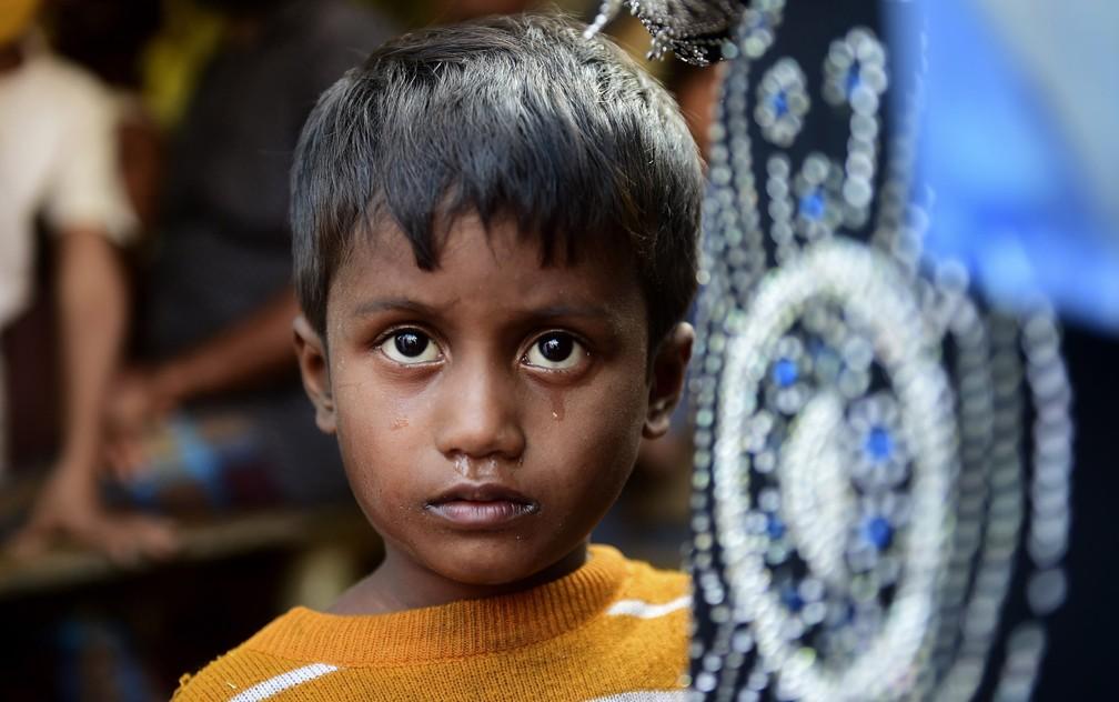 Criança posa para foto perto de um campo de refugiados em Teknaf, Bangladesh. Ele cruzou a fronteira com uma vizinha e a prima de 6 anos, cuja mãe está desaparecida. A polícia local diz que dezenas de migrantes foram presos e serão devolvidos para Mianmar — Foto:  Munir Uz Zaman/AFP