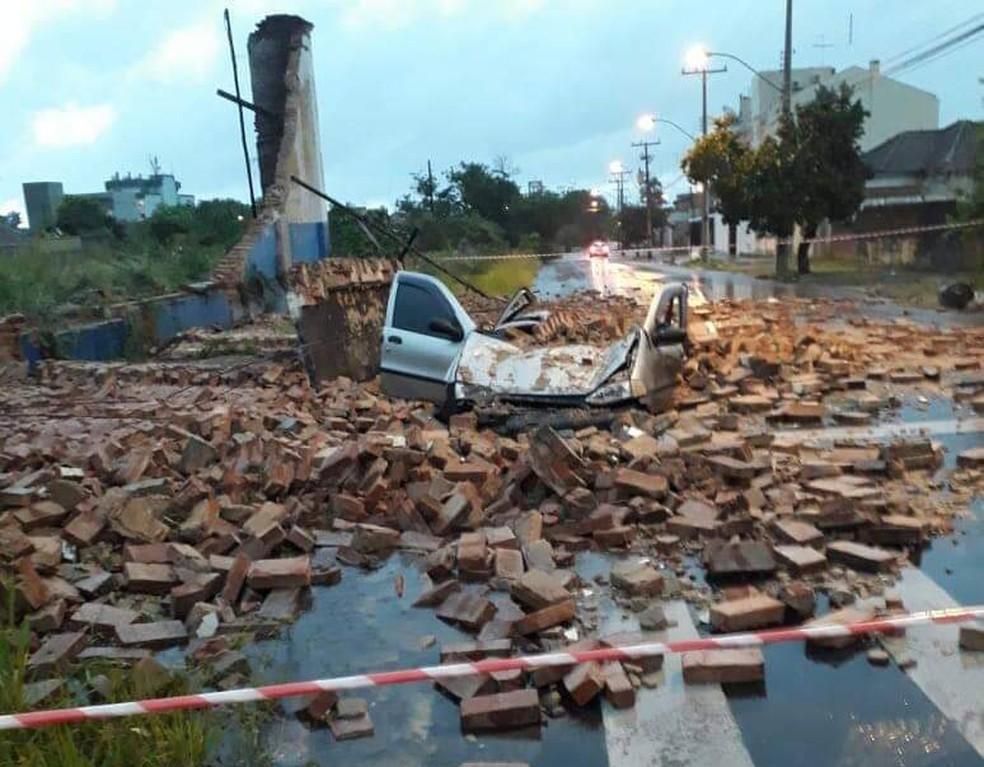 Carro ficou destruído por muro de empresa, que desabou durante chuva em São Leopoldo — Foto: Divulgação/Defesa Civil de São Leopoldo