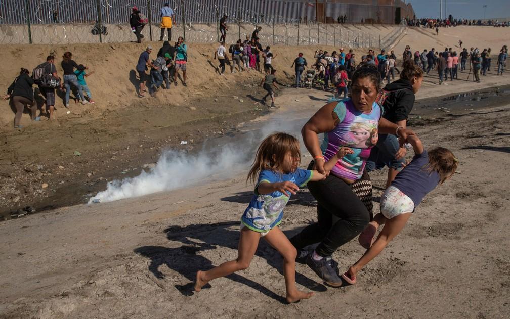 Maria Meza, migrante de Honduras, carrega suas filhas gêmeas de cinco anos para escapar de gás lacrimogêneo em Tijuana, na fronteira entre México e Estados Unidos, em 25 de novembro de 2018 — Foto: Reuters/Kim Kyung-hoon/File Photo