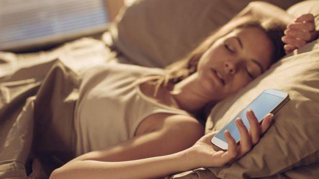Ao invés de colocar o celular no modo soneca, o ideal é abrir as cortinas e se expor à luz (Foto: Getty Images/BBC)